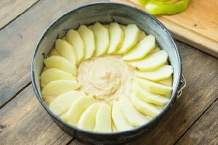 Выложить тесто с яблоками в форму