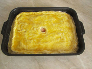 Смажьте верх пирога яйцом