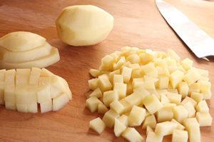 Очищенный картофель порежьте небольшими кубиками